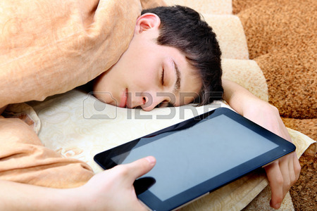 27492606-tired-teenager-sleeping-on-the-bed-with-tablet-computer